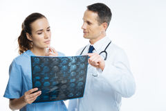 Medical professionals counseling over patient diagnosis together. Cooperative relations. Waist up shot of medical colleagues standing next to each other while Stock Photography