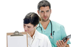 Medical professionals with paper in writing board. Against white background Stock Photos