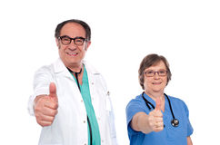 Medical professionals showing thumbs up. Mature medical professionals showing thumbs up at camera Stock Images