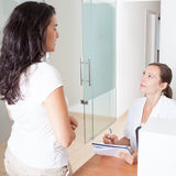 Medical recepcionist sets appointment with visitor. Office assistant with patient and agenda Royalty Free Stock Image