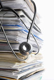 Medical record. Concept using stethoscope in front of pile of paper. Selective focus
