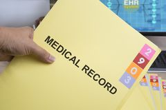 Medical record folder. Yellow medical record folder in someone hand Stock Images