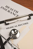 Medical record & health insurance. Patient's medical record with health insurance document in the background