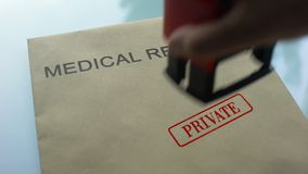 Medical records private, hand stamping seal on folder with important documents