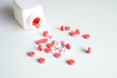 Medical red, pink and white pills. With plastic white bottle on white background royalty free stock image