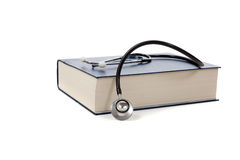 Medical reference book with a stethoscope on white. A medical reference book with a stethoscope on a white background stock photo