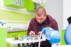 Medical repairman fixing equipment. Medical equipment engeneer fixing a dental chair in the office of the dentist Royalty Free Stock Photography