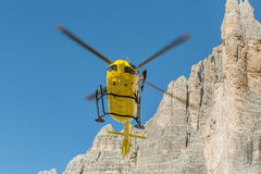 Medical rescue helicopter flying rescue injured climber on the Tre Cime. Italy, Dolomites Royalty Free Stock Photos
