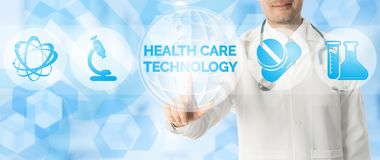 Doctor Points at HEALTH CARE TECHNOLOGY and Icons. Medical Research Concept - Doctor points at HEALTH CARE TECHNOLOGY with icons showing symbol of technology Stock Images