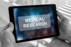 Medical research concept on a tablet. Male hands holding a tablet with medical research concept royalty free stock images
