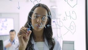 Medical research scientists writes scientific formula on a glass whiteboard.