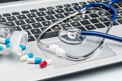 Medical Research, stethoscope and Capsule on laptop keyboard Stock Image