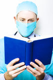 Medical research and study. A masked male doctor stands concentrating on the reference book that he is reading and assimilating in a medical research and study Royalty Free Stock Photography