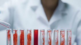 Medical researcher adding dry test material into the tubes with liquid, closeup. Stock footage Stock Images