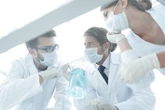 Medical researcher microbiology experiment in the laboratory. Scientists in the laboratory wearing protective goggles, looking at the flask stock image