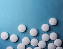 Medical round white tablets, calcium vitamins closeup on blue background with space for text or image. Pills royalty free stock photography