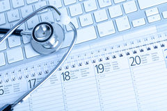 Medical Schedule. A stethoscope on a calender and a computer keyboard (blue tint Stock Image