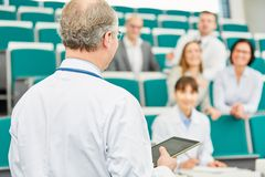 Medical school lecturer teach doctors. In lecture hall with tablet stock photos
