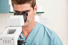 Medical or scientific researcher. Closeup of young male doctor viewing through microscope stock photo