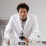 Medical scientist posing with microscope Stock Photos