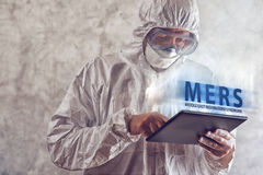Medical Scientist Reading About MERS Virus on Figital Tablet Com Stock Images