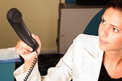 Medical Secretary Handing A Phone To The Doctor Royalty Free Stock Photos