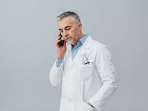 Medical service consultation by phone. Confident mature doctor having a phone call with his smartphone: medical service consultation by phone Royalty Free Stock Photos