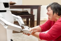 Free Medical Service Robot Is Giving A Mentally Disabled Woman The Ha Royalty Free Stock Photos - 118954018