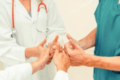 Doctor, surgeon and nurse join hands together. Medical service teamwork - Doctor, surgeon and nurse join hands together royalty free stock images