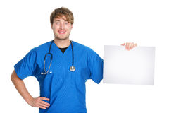 Medical sign. Male doctor / nurse showing and holding blank white paper sign board with copy space for text or message. Young medical professional caucasian stock photography