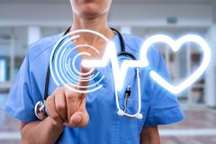 Medical sister at cardiology touching heart symbol. Medical sister at cardiology hospital touching heart symbol on invisible display with index finger royalty free stock image