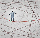 Medical Solution. Health care concept as a doctor walking on a red tightrope or highwire around a group of tangled wires as a symbol of challenges in insurance Royalty Free Stock Photo