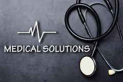 Medical solutions text on blackboard with stethoscope and heartbeat rate. Medical solutions text on chalkboard with stethoscope and heartbeat rate stock image