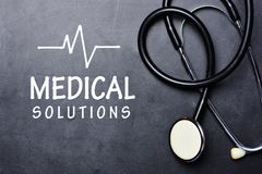 Medical solutions text on blackboard with stethoscope and heartbeat rate Stock Photography