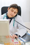 Medical speaking phone and working on computer Stock Photos