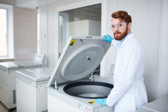 Medical specialist. Biochemist in whitecoat, gloves and protective eyeglasses standing by plasma centrifuge Royalty Free Stock Photo