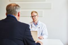 Medical specialist in office with patient. Talking and giving advice Stock Photos