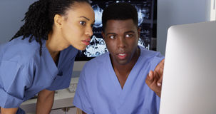 Medical specialist working with colleague on computer Stock Photo