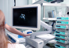 Medical specialists  in the hospital ward. Medical specialists near ultrasound machine in the hospital ward Royalty Free Stock Image