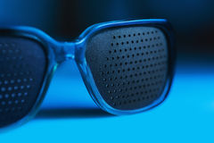 Medical spectacles with hole in blue backgrounds Royalty Free Stock Photo