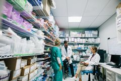 Medical staff discussing in hospital pharmacy. Doctors and nurse talking in hospital pharmacy Stock Photo