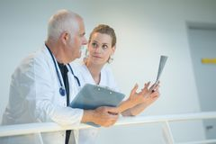 Medical staff in discussion leaning over balustrade stock image