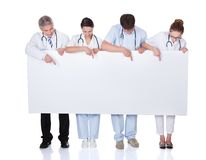 Medical staff holding up a white banner Royalty Free Stock Photo