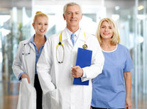 Medical staff. Image of successful healthcare worker at hospital. Portrait of medical assistant standing next to mature female doctor and senior doctor Stock Images