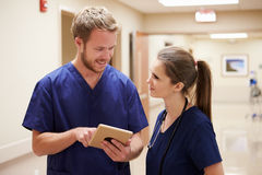 Medical Staff Looking At Digital Tablet In Hospital Corridor Stock Photo