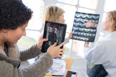 Medical staff looking at xrays and tablet screen. Medical royalty free stock photography