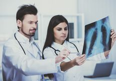 Medical staff looks at roentgen. Serious doctors. Doctors in dressing gown with stethoscope Royalty Free Stock Images