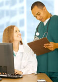 Medical Staff In Office. Medical staff working together in office environment. the woman in white coat sitting and the man in nurse uniform standing royalty free stock photo