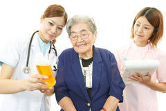 Medical staff with old woman Stock Photography