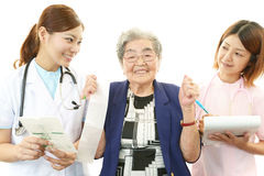 Medical staff with old woman Stock Images
